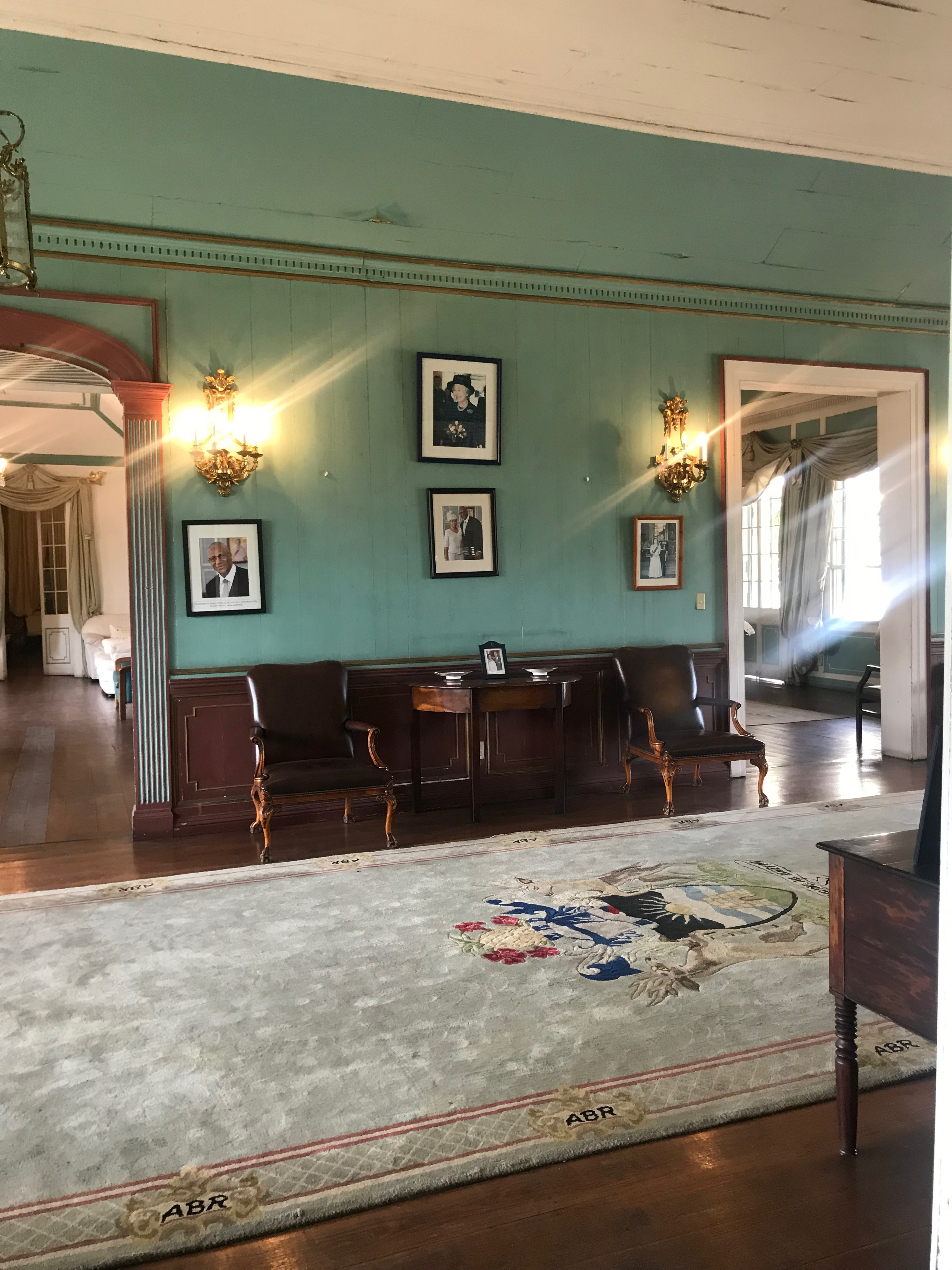 The entrance hall in the main house with photographs of the Governor General and Queen Elizabeth II