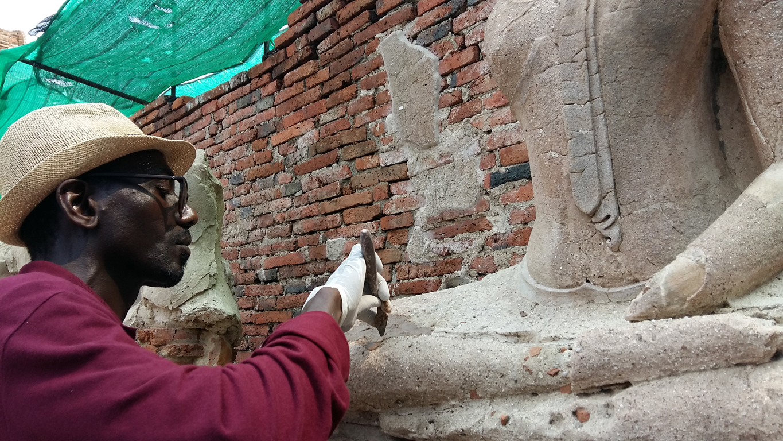 Ousmane Kounta working on stucco mortar for the Buddha statue
