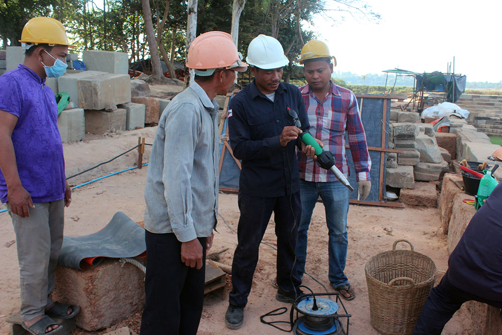 Phnom Bakheng site manager Mou Var, shown here in a blue uniform and white hard hat, explains to EFEO staff how to set the welding machine, 2017