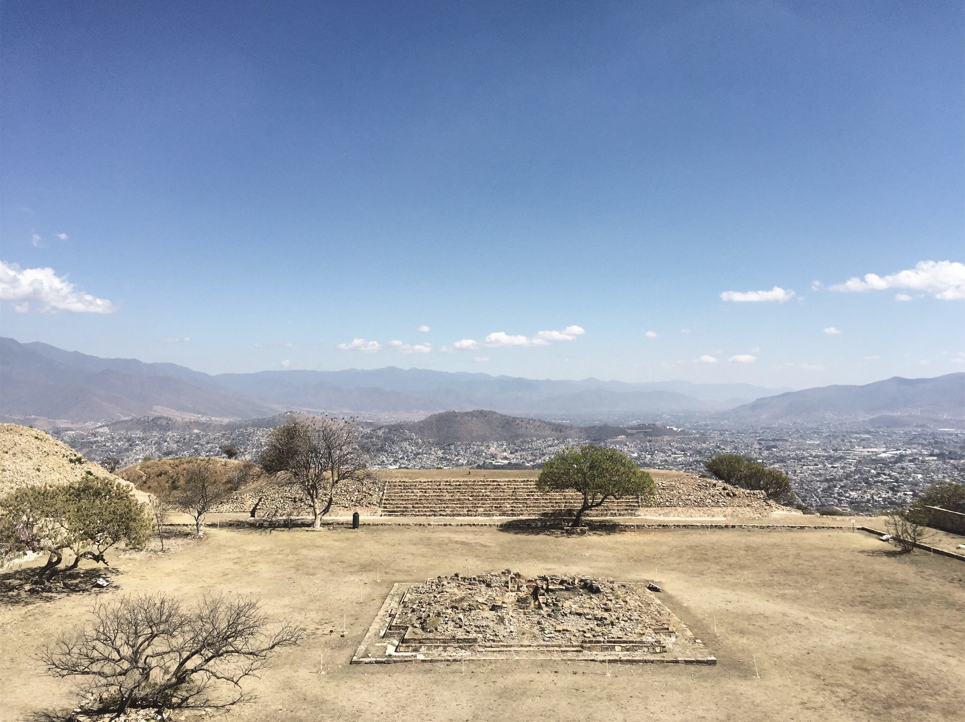 The view of Atzompa's highest square from the main pyramid and with the city of Oaxaca and its mountainous landscape in the background.