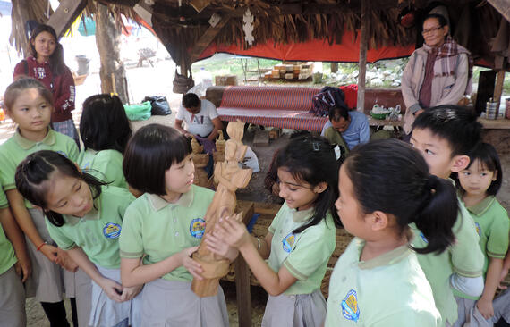 School children with a woodcarving example at Shwe-nandaw Kyaung, 2019