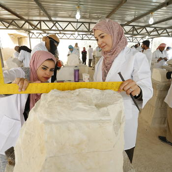Ayat and Balqees, Jordanian trainees, measure a block of local stone
