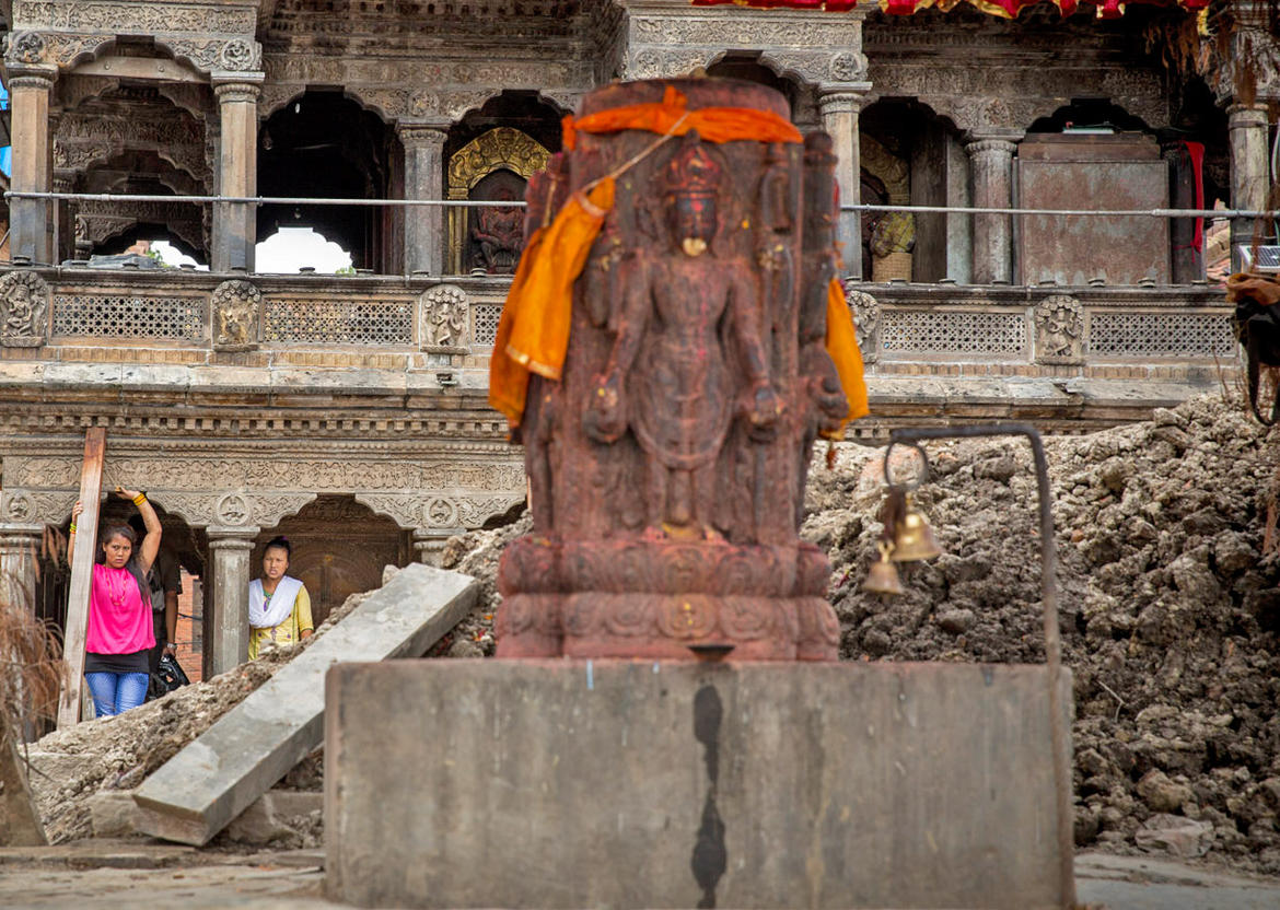 Looking past the idol and its temporary shelter atop the bare Char Narayan Plinth toward Krishna Mandir. KVPT aided in constructing the temporary shelter for the deity idol, so that community members could continue their daily puja rituals. Photo Scott Newman/KVPT.