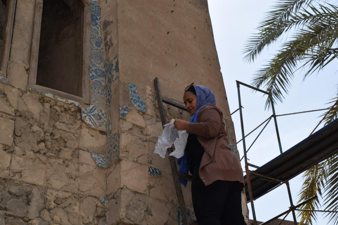 Abeer Saed Eledeen climbs a ladder to document the exterior of Takiyyat Ibrahim al-Gulshani.