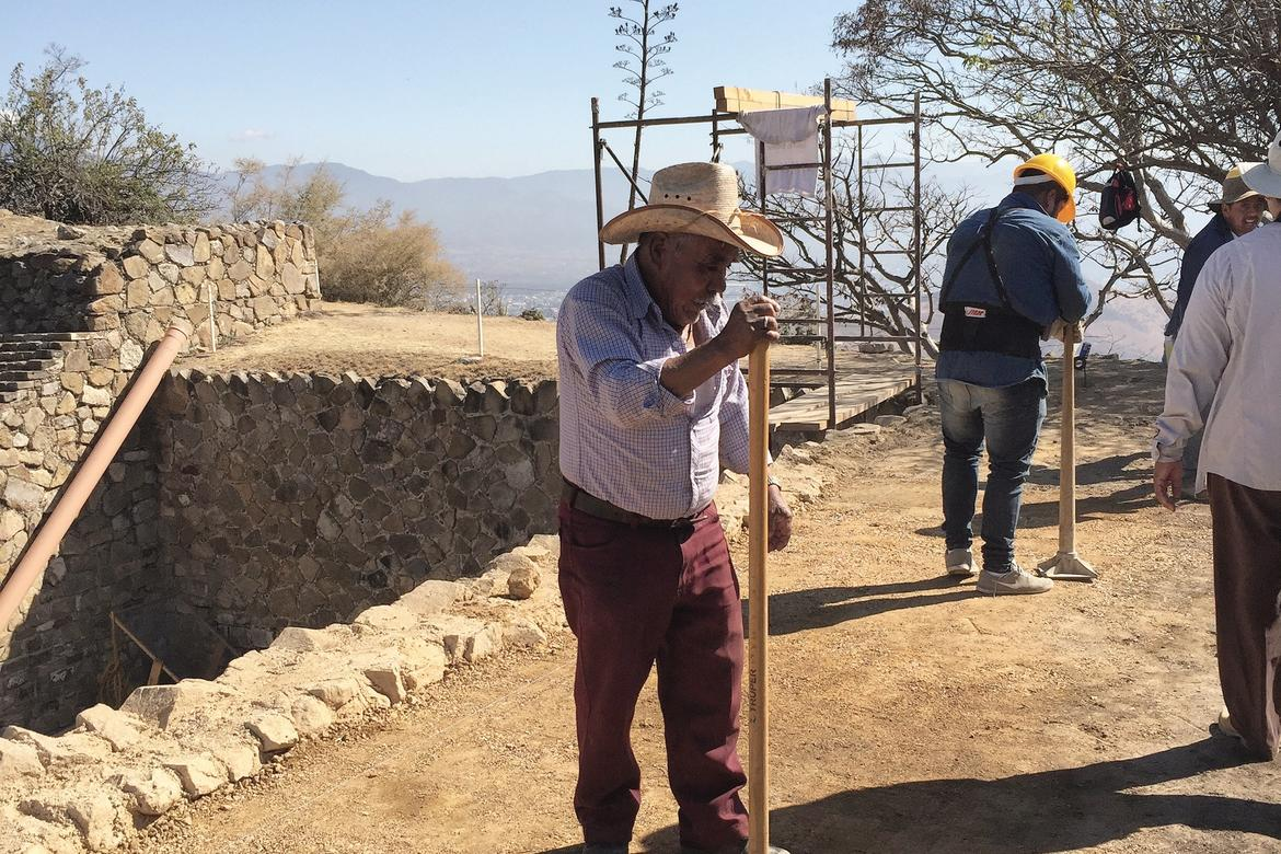 Conservation technicians compacting the ground on top of the perimeter wall of the ball court  area.