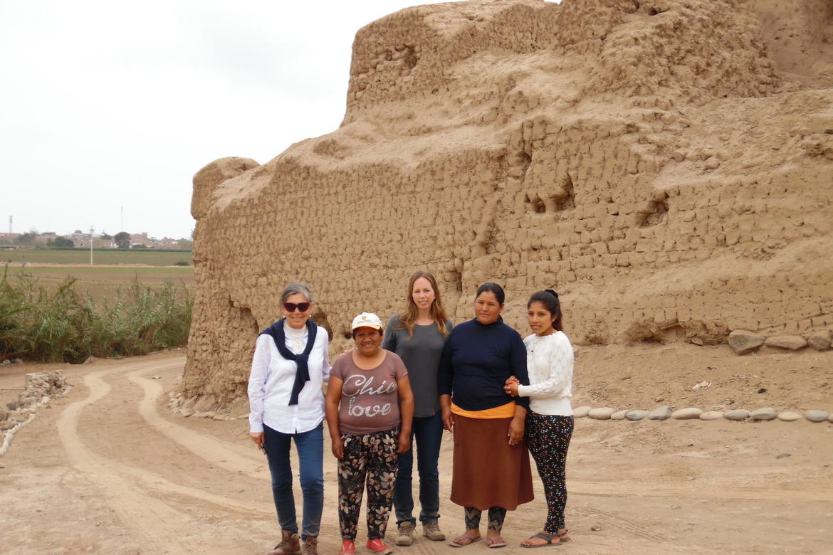 Martha Zegarra (Executive Director, WMF Peru), Francesca Fernandini (Archaeological Program Director, Cerro de Oro), and a group of local women stand in front of the wall that surrounds the site.