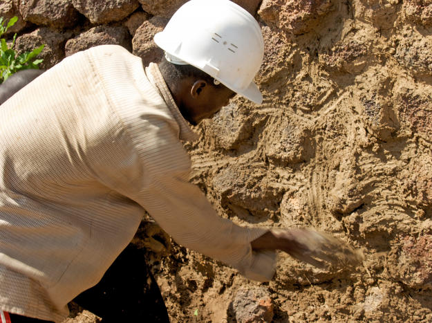 A conservator maintains a section of the stone and earthen rampart complex, 2010
