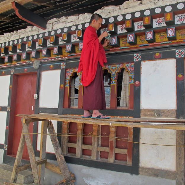 A monk paints the conserved sections of the building, 2012