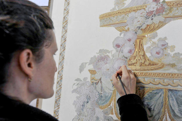 A conservator works on the interior paintings , 2012