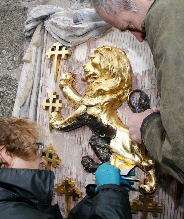 Conservators gilding the monument's lion, 2012