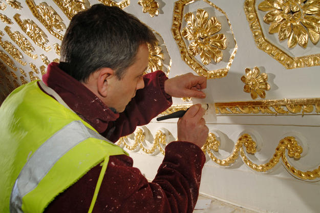 Conservator applying gilding to library ceiling, 2010