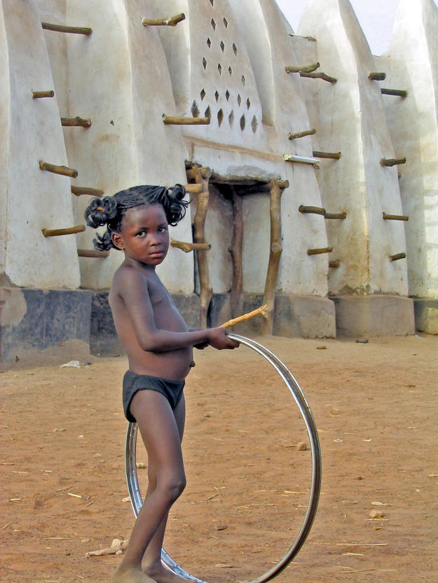 A young villager plays outside the mosque, 2004