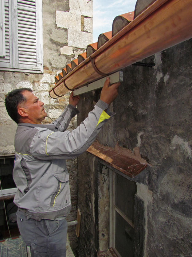 Installing a new copper gutter on the southern side of the roof , 2014