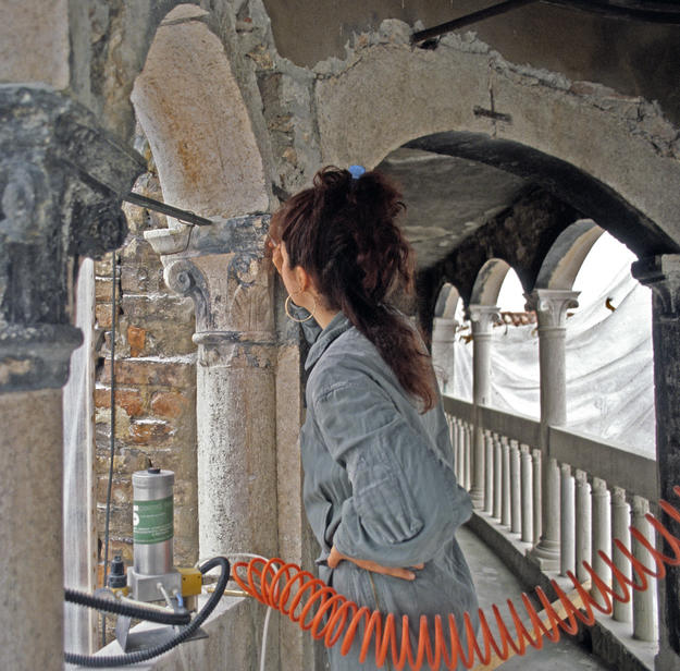 A conservator removes corrosive deposits that have blackened the column's capital, 1981
