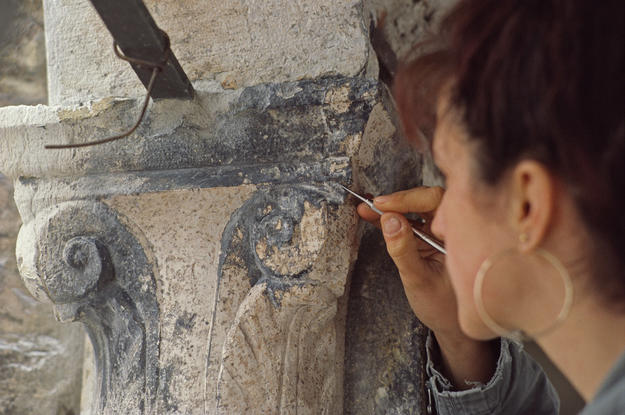 A conservator cleans one of the capitals, 1981