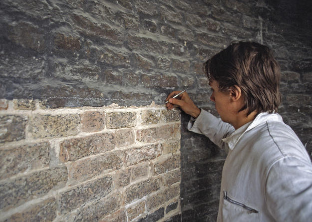 A conservator removes the destructive stuccatura from the structure's bricks, 1981