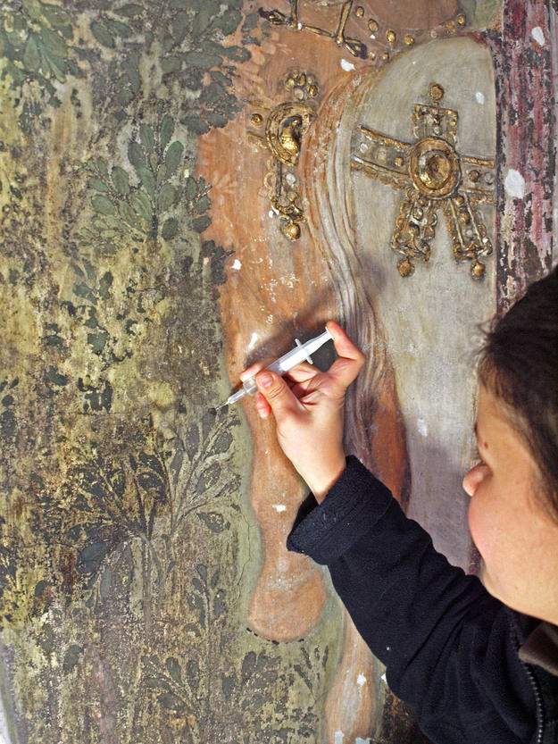 A conservator consolidating part of the fresco, 2012