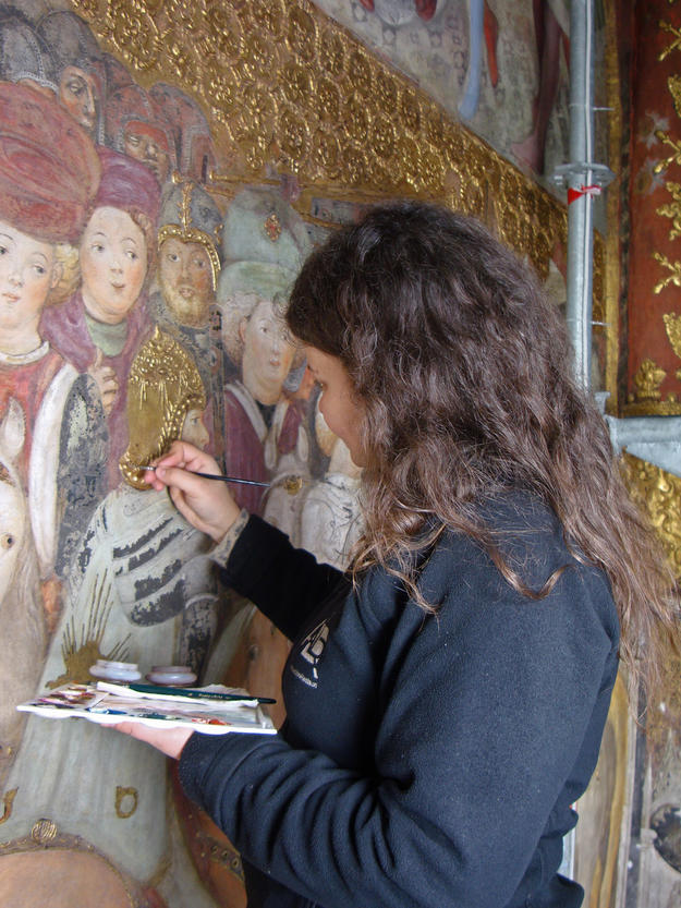 A conservator works on the fresco, 2014