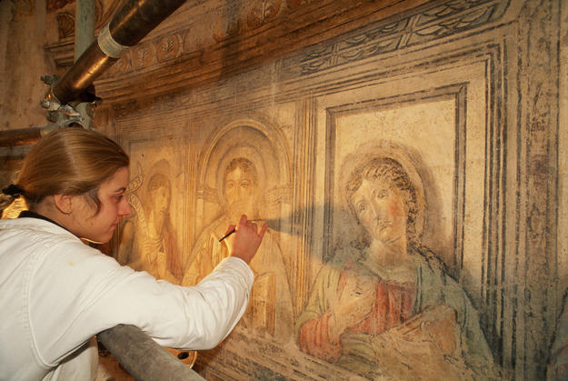 A conservator treating the lower registers of the frescoes on the wall of the circular cella, 1997