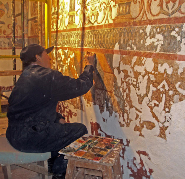 A conservator preserving the wall paintings , 2012
