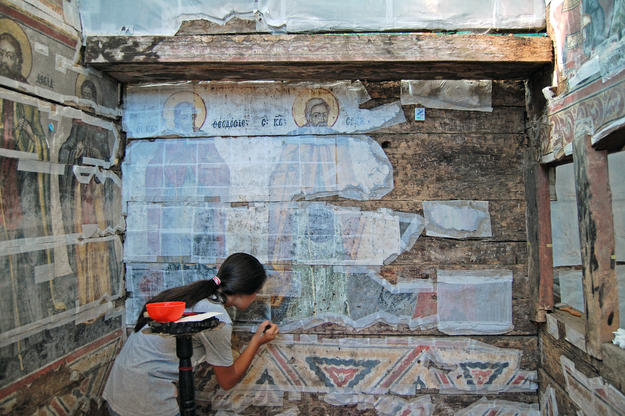 A conservator consolidates the exisiting painting at Ursi, 2013