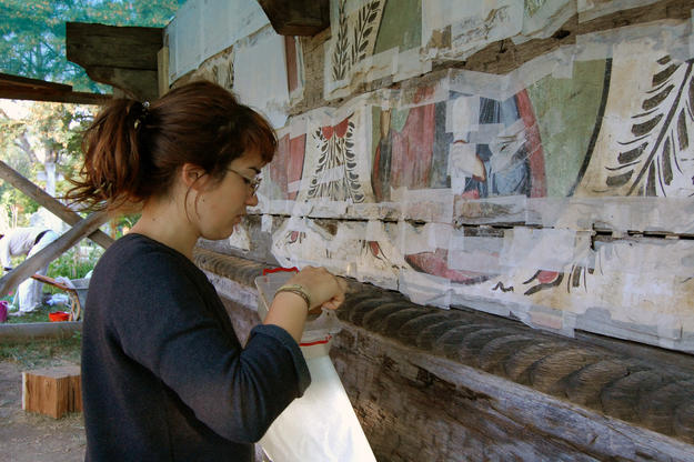 A conservator preserves wall paintings at the Church of Ursi, 2013