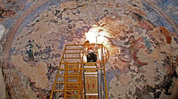 A conservator examines the murals of the Capilla del Rosario, 2004