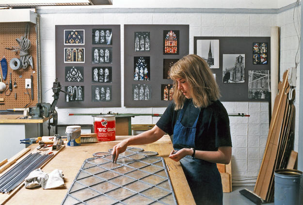 A conservator applies putty to new glazing, 1990