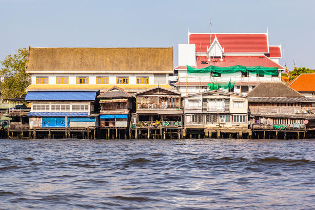 Houses elevated on stilts lie on the Chao Phraya riverside.