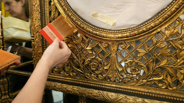 Conservator applying gold leaf
