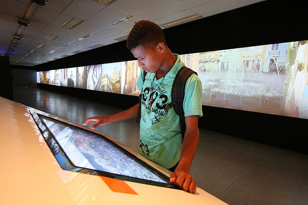 A visitor to the exhibition enjoys the interactive media, 2013