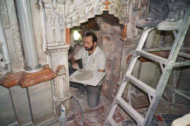 A mason carries out repairs in the interior masonry cladding, in the opening between the Chapel of the Angel and the Tomb Chamber, 2016