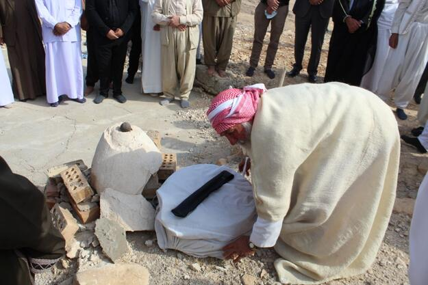 One of the clergymen in Sinjar places holy dirt on the site of the shrine to bless it, 2020.