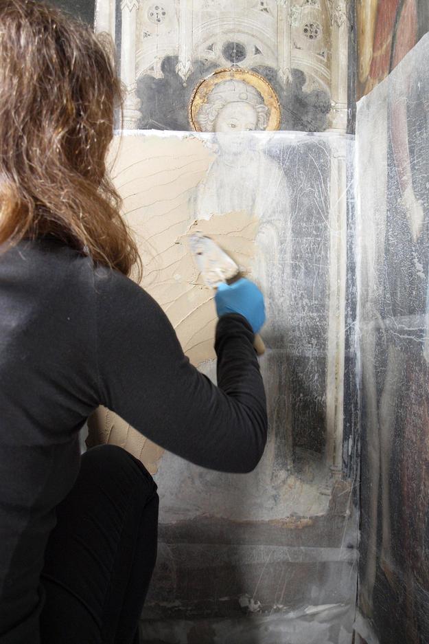 A conservator removes salt from Scene 33, 2015