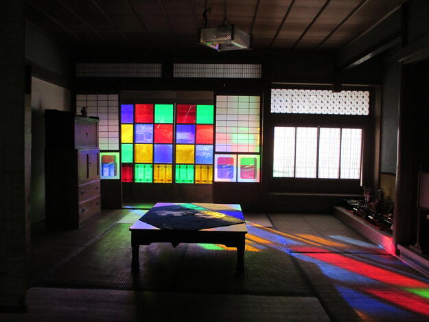A historic view of the interior of Konishi Honke, known also as the House of Colored Glass, after the windows of the main room on the upper floor were replaced with colored glass in the early twentieth century.