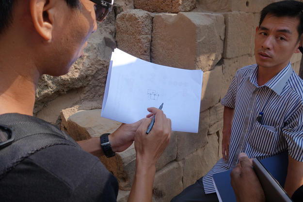 Hun Bunwat, WMF Architect (left) and Chiv Phirum, WMF Engineer (right) discuss the reassembly of the wall at Level E on the south side of Phnom Bakheng, 2015