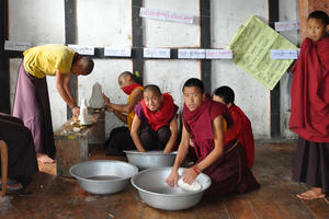 Monks preparing votive offerings, July 2010