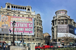 """A pair of early twentieth-century buildings on Bucharest's Independence Embankment, including the """"Adriatica"""" Society Palace (left), illustrate the degradation of the urban experience caused by commercial advertising, 2011"""