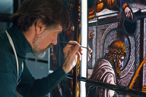 Craftsman Erik Erickson in-painting a restored glass insert to be discernable as a modern intervention only upon close examination., 1990