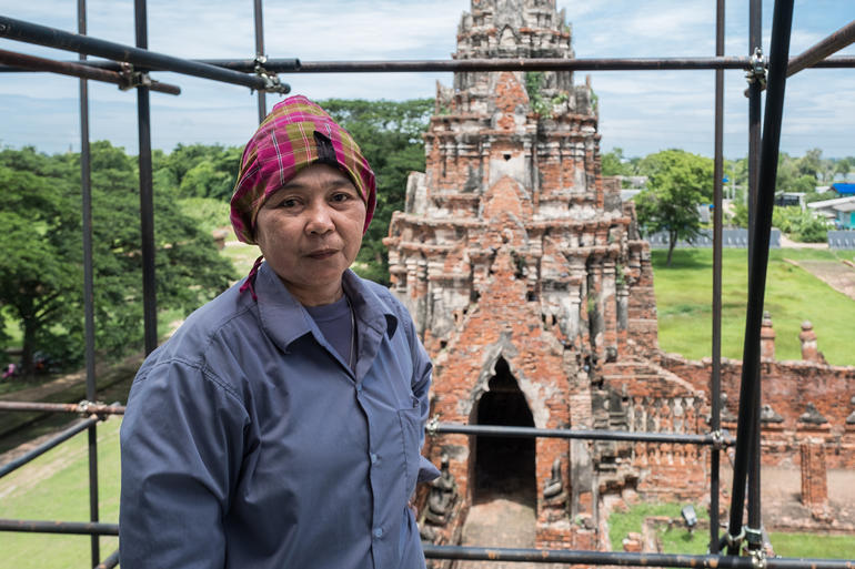 Conservator Khun Peng poses on scaffolding at Wat Chaiwatthanaram.
