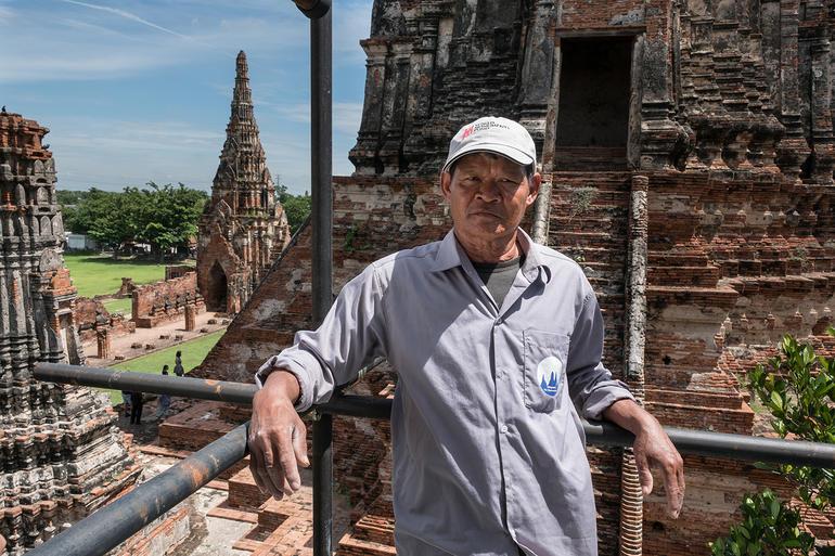 Khun Tee poses on scaffolding at Wat Chaiwatthanaram.
