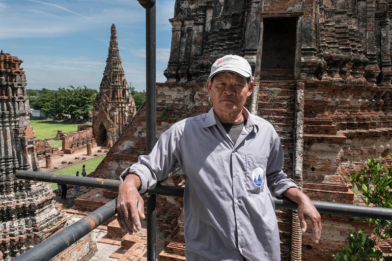 Khun Tee poses on scaffolding at Wat Chaiwatthanaram.