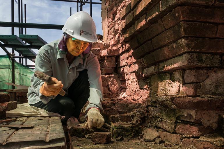 Chief mason Mali Choomchooboon works on the brick.