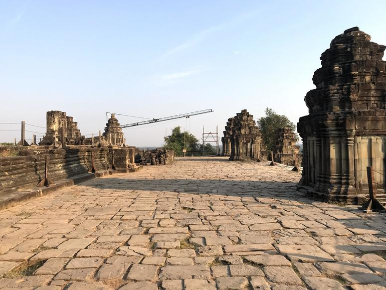 A crane in the distance, surrounded by stone shrines, atop Phnom Bakheng.