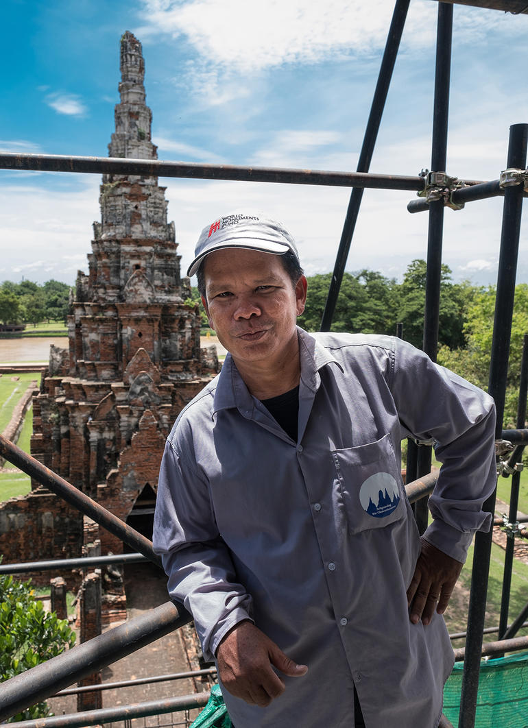 Conservator Khun Kee poses on scaffolding at Wat Chaiwatthanaram.