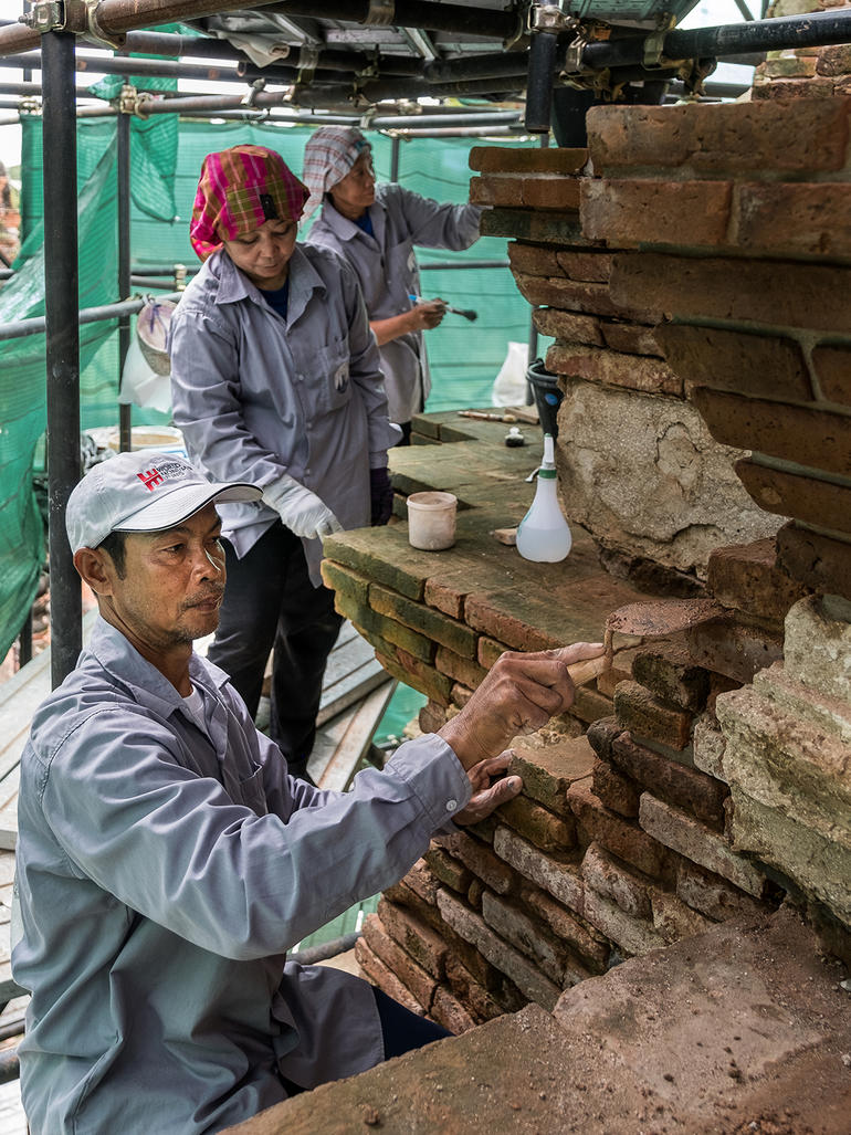 Khun Nu, Khun Peng, and Khun Mali on Meru C3 performing masonry conservation techniques.