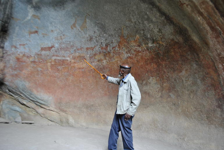 David Ngwenya, a local steward of Matobo Hills Cultural Landscape in Zimbabwe, stands in front of its endangered rock art.