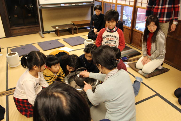 Fusae Kojima, front, educates children on machiya traditions.