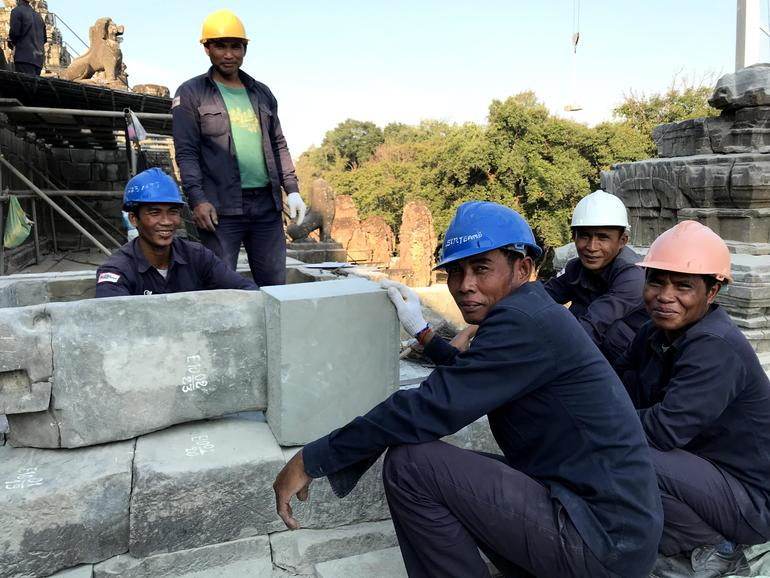 Skilled workers at Phnom Bakheng rebuild stone shrines after waterproofing.