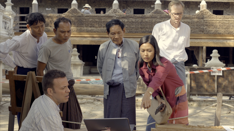 Thander Phyo discusses woodcarving quality with site technicians.
